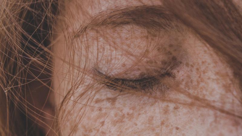 Ein geschlossenes Auge einer rothaarigen Frau.