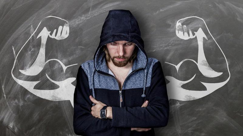 Ein Mann steht vor einer Wandtafel. Auf der Tafel sind muskulöse Oberarbe zu sehen.