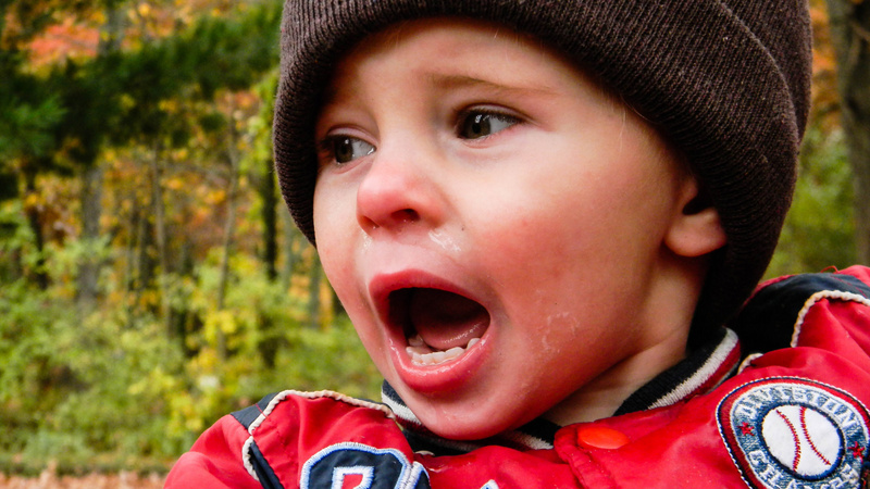 Schmerzen, weh tun, Aua: Kleines Kind mit Mütze und Winterjacke schreit und weint.