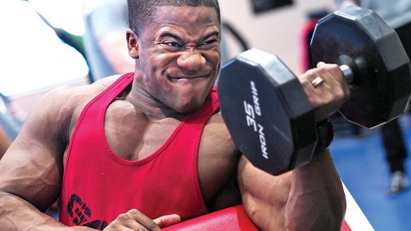 Schwarzer Mann mit vielen Muskeln in einem roten T-Shirt stämmt Gewicht.
