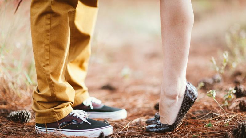 Des mollets de deux personnes, une femme sur la pointe des pieds et un homme.