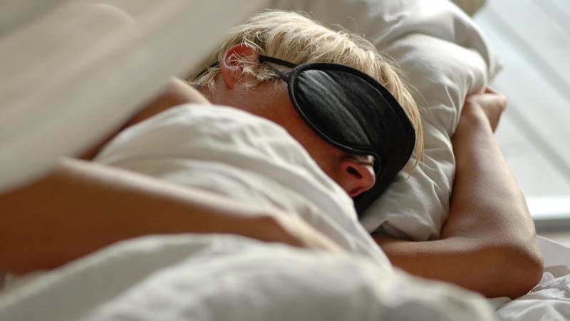 Schlafen, Schlafstörungen: Frau mit kurzen blonden Haare liegt in einem Bett mit weisser Bettwäsche, sie trägt eine schwarze Schlafbrille