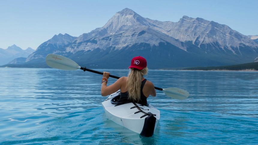 Eine Frau mit Kayak auf dem See.