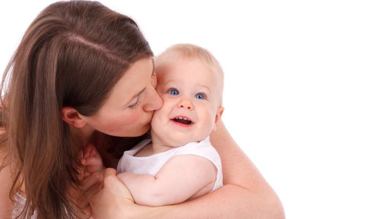 Ernährung, Babynahrung, Stillen: Frau hält Baby im Arm und küsst es auf die Wange.