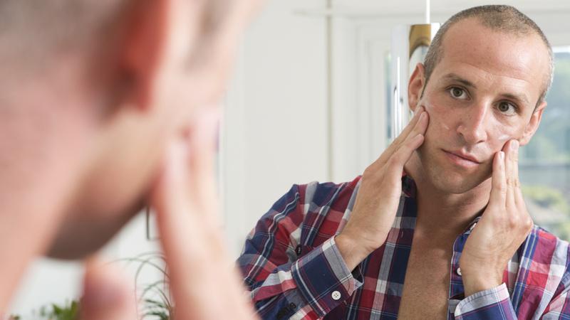 Schönheit, Pflege, Gesicht, Haut: Mann in kariertem Hemd mit kurz geschorenen haaren sieht in einen Spiegel und reibt sich mit beiden Händen ein Pflegeprodukt auf die Wangen