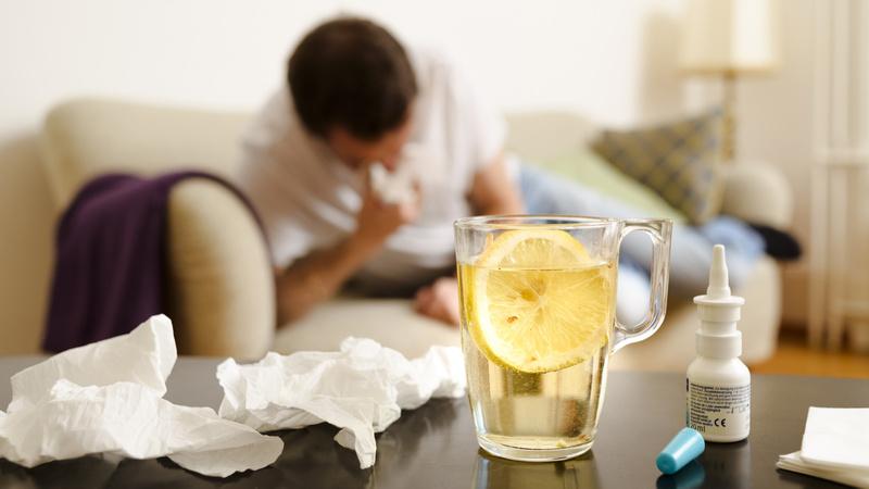 Erkältung, Schnupfen, krank: Mann liegt Naseschnäuzend auf dem Sofa, im Vordergrund eine Tasse Tee, Nasenspray und gebrauchte Papiertaschentücher