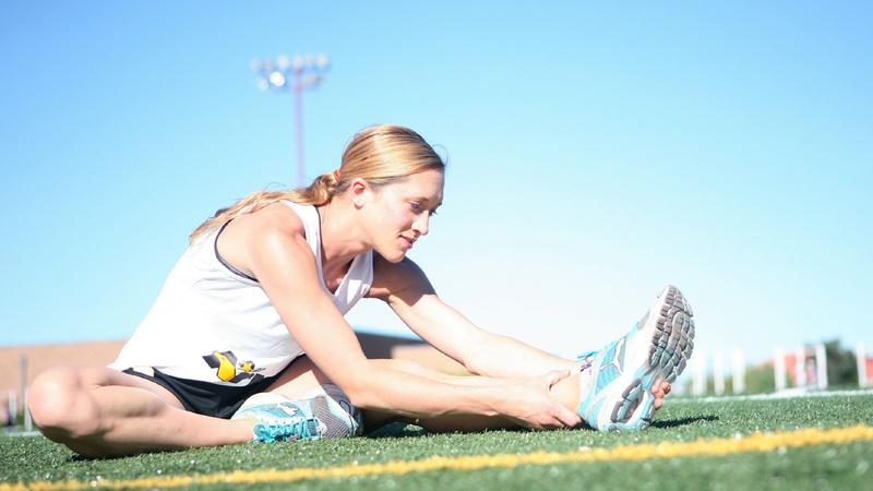 Fitness, Trainingstipps, Warm-up: Frau in Sportkleidung sitzt auf einem Rasen. Sie hat ein Bein angewinkelt und das andere ausgestreckt. Sie hält die Knöchel des ausgestreckten Beins fest und beugt ihren Oberkörper darüber