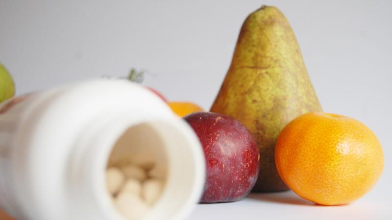 Mineralstoffe, Vitamine, Vitalstoffe, Immunsystem: Plastikdöschen liegt geöffnet auf der Seite, darin Vitaminpillen. Im Hintergrund eine Birne, eine Mandarine und eine Pflaume
