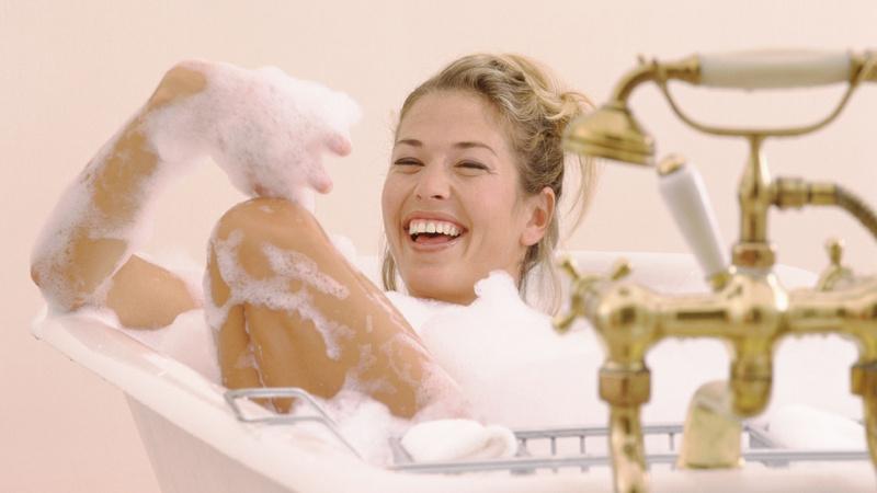 Ernährung, Tee, Baden: Frau mit hochgesteckten blonden Haaren sitzt i einer Badewanne mit goldfarbenen Armaturen. Sie lacht