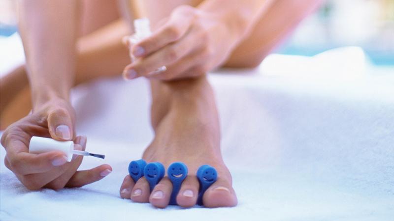 Schönheit, Pflege, Fusspflege, Füsse: Fuss und Hände einer Frau. Sie hat die Zehen in einem blauen Zehenspreizer und ist gerade dabei, die Nägel zu lackieren.