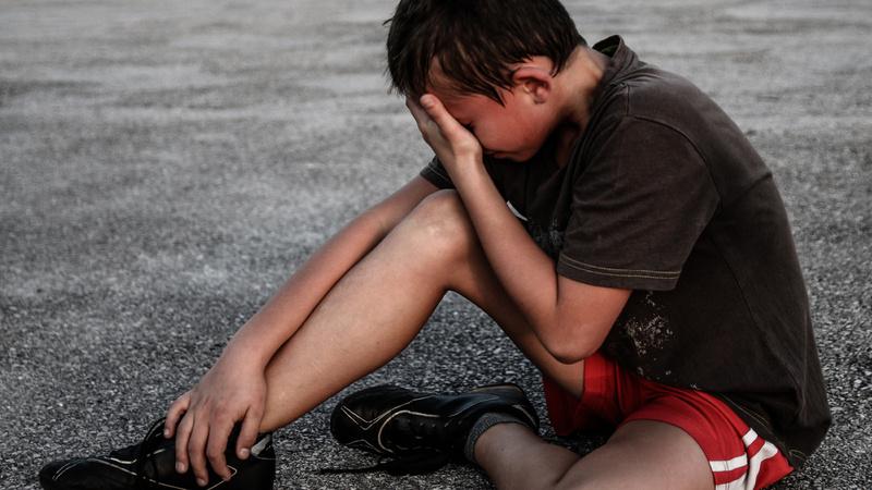 Schmerzen, Schmerzarten: Bub sitzt auf dem Boden, hält sich das Bein und verdeckt seine Augen mit der Hand. Er weint.