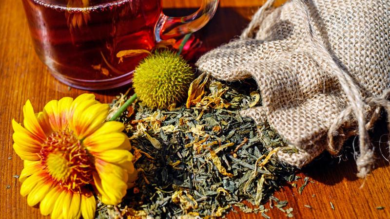 Ein Jutesäcklein, daraus fallen getrocknete Kräuter sowie eine ganze gelbe Blüte. Dahinter eine durchsichtige Tasse mit Tee