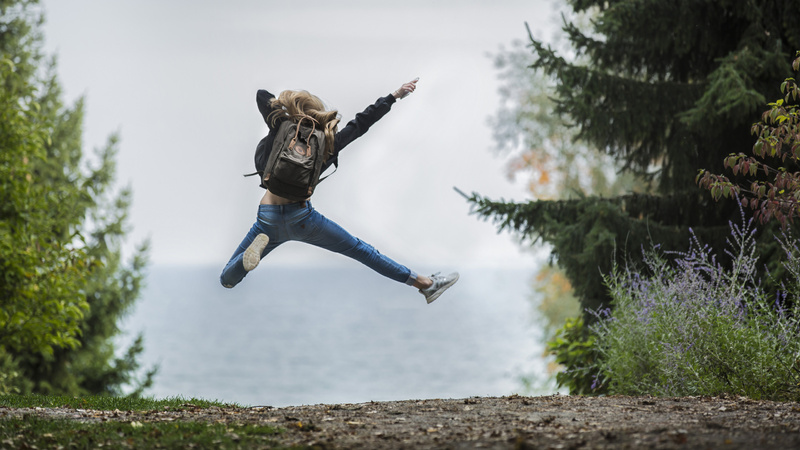 Glück, Stress, Wohlfühlen: Ein Waldweg. Eine junge Frau von hinten. Sie springt fröhlich in die Luft.