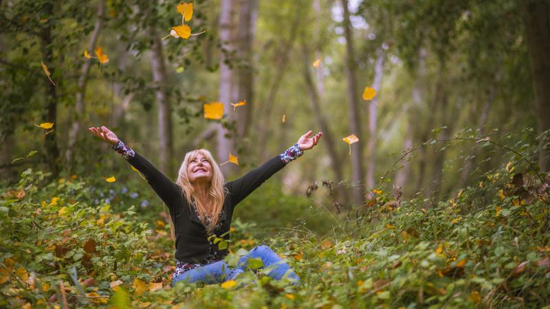 Wald, Waldbaden, Bäume: Frau sitzt mitten im Wald am Boden, hat die Arme in die Höhe gestreckt. Auf sie fallen bunte Herbstblätter hinunter.