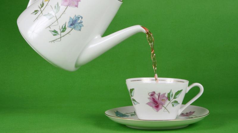 Ernährung, Tee, trinken, Schwarztee: Teegeschirr, weiss mit zartem Blumenmuster bemalt. Aus der Kanne schenkt jemand Tee in die Tasse, der Hintergrund ist grasgrün