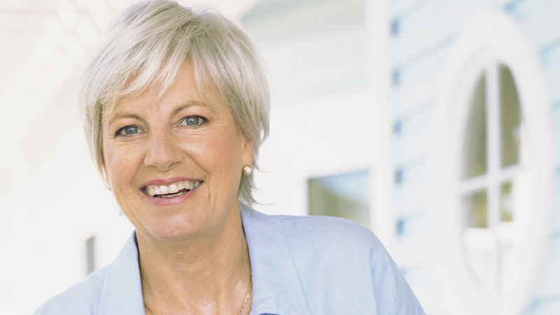 Schönheit, Pflege, Mundpflege, Zähne: Frau mittleren Alters mit grauen kurzen Haaren in einer blauem Bluse steht vor einem weissen Haus, sie lächelt und zeigt schöne gepflegte Zähne.