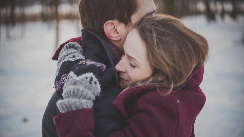Frieren, Schnee, Winter, Kälte, Eis: Ein Mann und eine Frau in Winterkleidern umarmen sich.