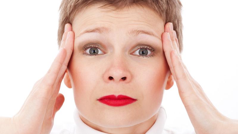 Wellness, Massage, Selbstmassage: Frau mit kurzen braunen Haaren unr rot geschminkten Lippen massiert sich mit beiden Händen die Schläfen