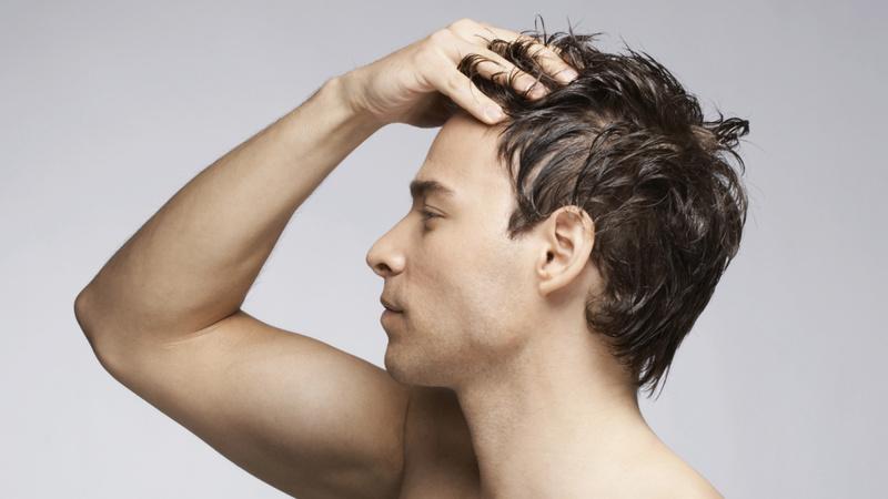 Haarausfall, Glatze: Junger Mann mit kurzen braunen Haaren fährt sich mit der rechten Hand durchs Haar