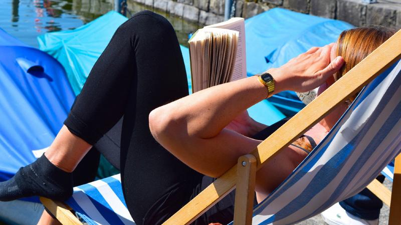 Eine Frau im Liegestuhl liest ein Buch.