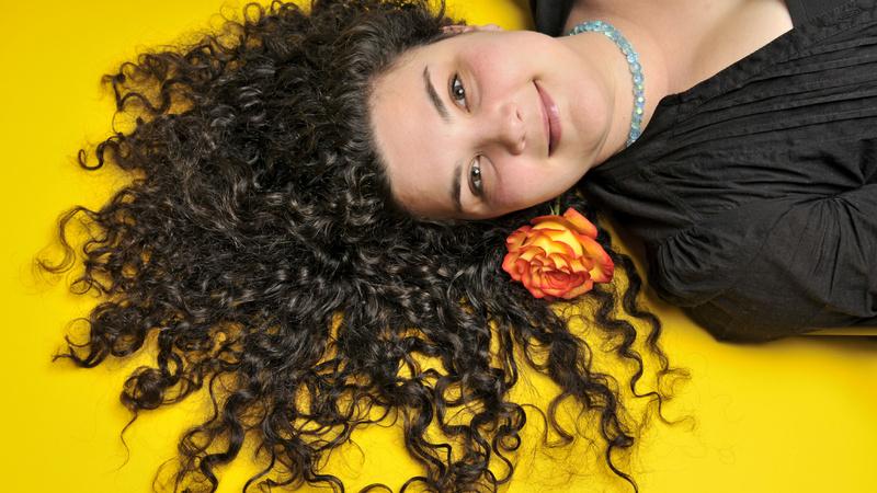 Schönheit, Pflege, Haare: Junge Frau mit langen schwarzen Locken liegt auf dem Rücken, ihre Haarpracht zum Fächer ausgebreitet. Im Haar steckt eine rote Blume.