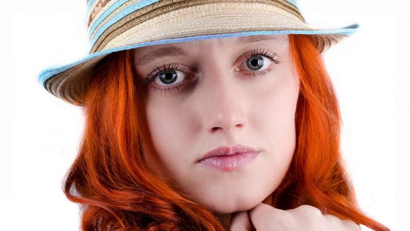 Schönheit, Pflege, Couperose, Gesicht: Sehr blasse Frau mit langen roten Haaren trägt einen Strohhut