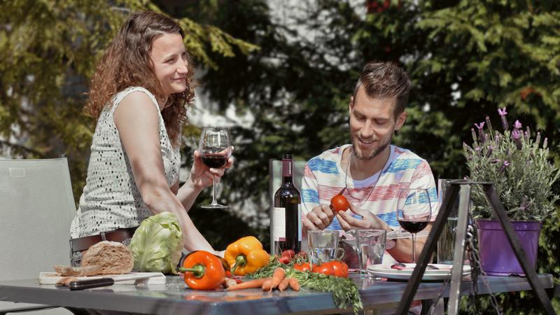 Ernährung, Mythen, Gesund: Junges Pärchen sitzt im Garten am Tisch und bereitet ein Essen aus frischen Zutaten zu.