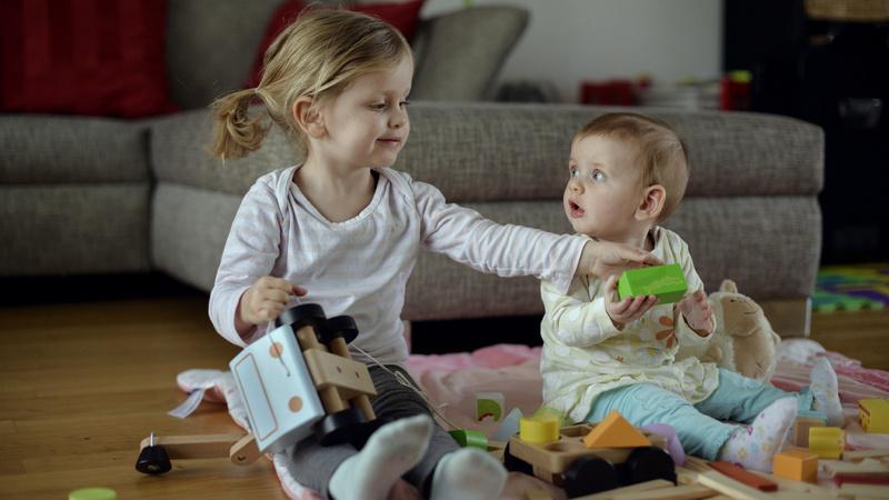Baby, Unfälle, Krankheiten, Hausapotheke: Baby sitzt mit grosser Schwester auf dem Boden. Sie spielen miteinander.