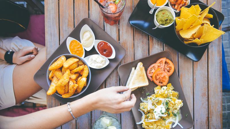 Ernährung, Mengen, Ungesund: Tisch von oben, Frauenarm ist zu sehen. Auf dem Tisch verschiedene Teller mit Esswren.